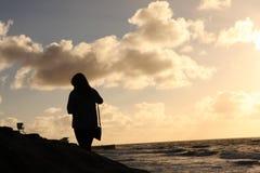 Силуэт женщины океаном на заходе солнца Стоковые Фото