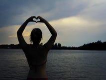 Силуэт женщины показывая знак сердца перед озером в лете Стоковая Фотография RF