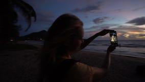 Силуэт женщины принимая фото selfie с мобильным телефоном во время захода солнца на пляже акции видеоматериалы