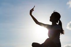 Силуэт женщины принимая selfie с мобильным телефоном под горизонт i Стоковые Изображения RF