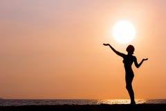 Силуэт женщины при шляпа стоя на предпосылке моря Стоковые Фотографии RF