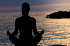 Силуэт женщины размышляя в положении лотоса морем на заходе солнца изолированная белизна вид сзади Стоковое Изображение