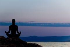 Силуэт женщины размышляя в положении лотоса морем на заходе солнца изолированная белизна вид сзади Стоковые Изображения