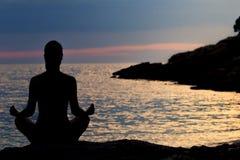 Силуэт женщины размышляя в положении лотоса морем на заходе солнца изолированная белизна вид сзади Стоковая Фотография