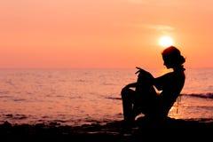 Силуэт женщины сидя на назад освещенной предпосылке моря Стоковые Изображения