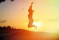 Силуэт женщины скача на пляж Стоковые Изображения RF