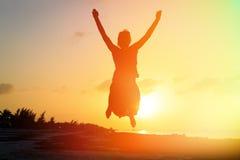 Силуэт женщины скача на пляж Стоковые Изображения