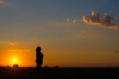 Силуэт женщины стоя на луге во время захода солнца лета Стоковая Фотография