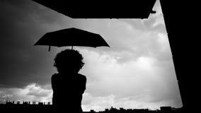 Силуэт женщины с зонтиком стоковые изображения