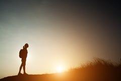Силуэт женщины укладывая рюкзак с заходом солнца Стоковое Изображение