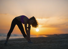 Силуэт женщины фитнеса делая тренировку на пляже на сумраке Стоковая Фотография RF