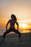 Силуэт женщины фитнеса делая тренировку на пляже на сумраке Стоковое фото RF