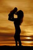 Силуэт женщины целуя младенца стоковые изображения rf