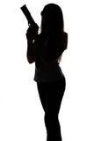 Силуэт женщины шпионки с оружием стоковые изображения