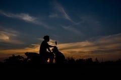 Силуэт женщин сидя на мотоцикле Стоковые Изображения