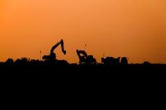 Силуэт затяжелителя экскаватора на строительной площадке, Backhoe силуэта стоковые фото