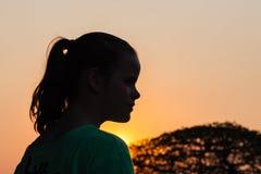 Силуэт захода солнца девушки молодой Стоковые Фото