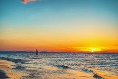 Силуэт захода солнца пляжа Стоковые Изображения