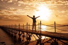 Силуэт захода солнца человека наблюдая стоковое изображение rf