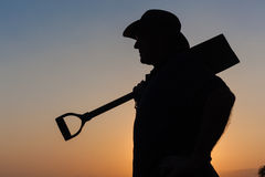 Силуэт захода солнца человека работника стоковая фотография