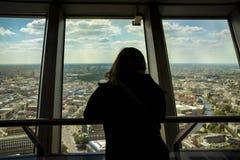 Силуэт заднего взгляда женщины смотря из окна на Стоковая Фотография