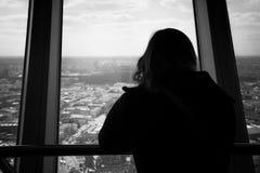 Силуэт заднего взгляда женщины смотря из окна на Стоковое фото RF