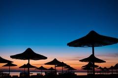 Силуэт зонтика пляжа на пляже в сумерк Стоковые Изображения