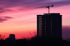 Силуэт здания под конструкцией во время захода солнца Стоковые Изображения RF