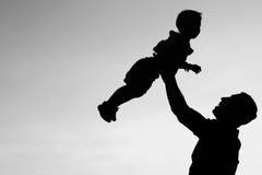 Силуэт игры отца и сына Стоковая Фотография