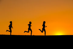 Силуэт идущих детей против захода солнца Стоковое фото RF
