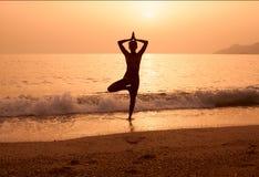 Силуэт йоги девушки практикуя на пляже моря Стоковые Фотографии RF