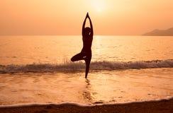 Силуэт йоги девушки практикуя на пляже моря Стоковые Фото