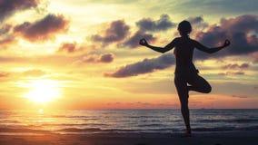 Силуэт йоги женщины на заходе солнца моря Стоковое Фото