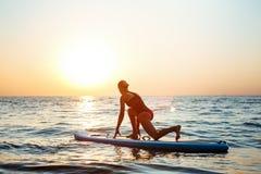 Силуэт йоги красивой девушки практикуя на surfboard на восходе солнца Стоковые Изображения