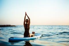 Силуэт йоги красивой девушки практикуя на surfboard на восходе солнца Стоковое фото RF