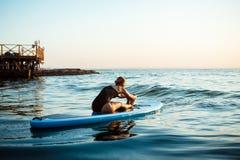Силуэт йоги красивой девушки практикуя на surfboard на восходе солнца Стоковые Фотографии RF