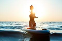 Силуэт йоги красивой девушки практикуя на surfboard на восходе солнца Стоковые Изображения RF