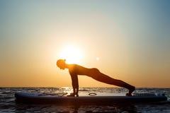 Силуэт йоги красивой девушки практикуя на surfboard на восходе солнца Стоковое Изображение RF