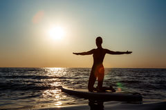 Силуэт йоги красивой девушки практикуя на surfboard на восходе солнца Стоковая Фотография RF