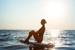 Силуэт йоги красивой девушки практикуя на surfboard на восходе солнца Стоковое Изображение