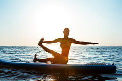 Силуэт йоги красивой девушки практикуя на surfboard на восходе солнца Стоковое Фото
