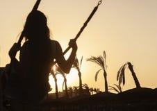 Силуэт катания маленькой девочки на качании на заходе солнца на задней части стоковая фотография rf