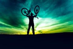Силуэт, контур велосипеда и праздновать byciclist поднимая Действие состязания успешных людей выигрывая стоковые фотографии rf
