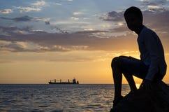 Силуэт корабля над восходом солнца и силуэт подростка Стоковая Фотография