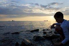 Силуэт корабля над восходом солнца и силуэт подростка Стоковые Фотографии RF