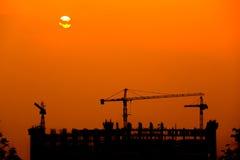 Силуэт крана башни на строительной площадке на заходе солнца Стоковое Фото