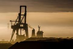 Силуэт крана и корабль показывают против пестротканого захода солнца Стоковая Фотография RF