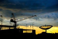 Силуэт крана и спутниковой антенна-тарелки Стоковая Фотография