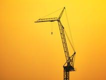 Силуэт крана конструкции на небе захода солнца Стоковая Фотография