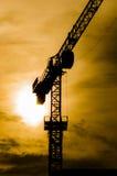 Силуэт крана конструкции с холодной предпосылкой захода солнца Стоковая Фотография